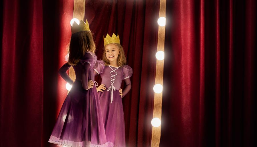 Little girl in princess costume standing in front of full length mirror